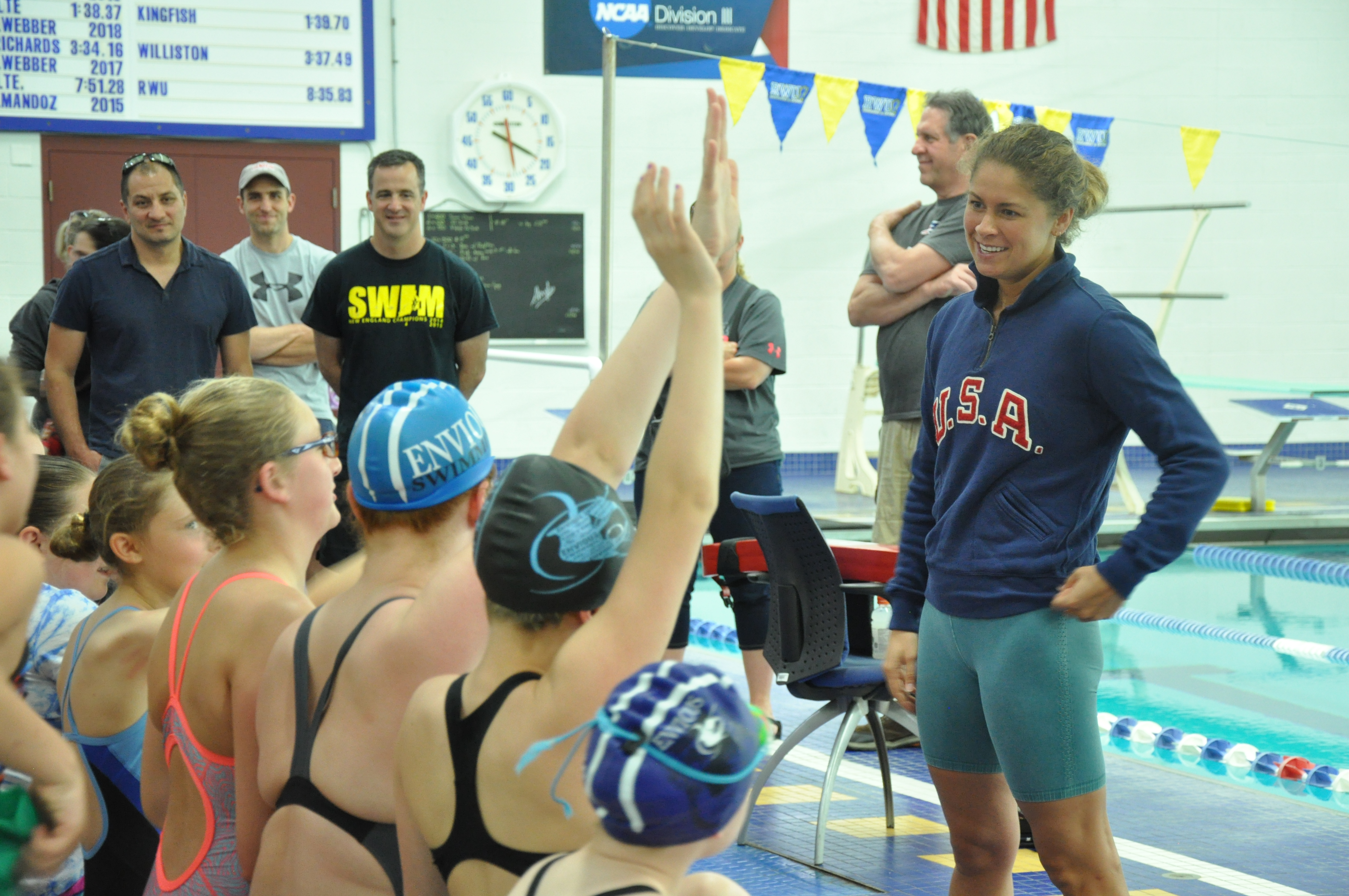 A group of young swimmers face away from the camera, raising hands. Olympic swimmer Elizabeth Beisel stands smiling before them, taking questions, wearing a blue