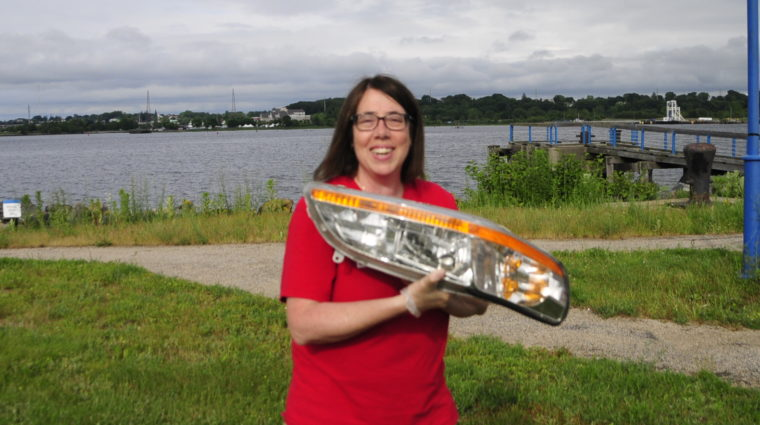Save The Bay Volunteer Manager July Lewis holds a headlight found at Collier Point Park.