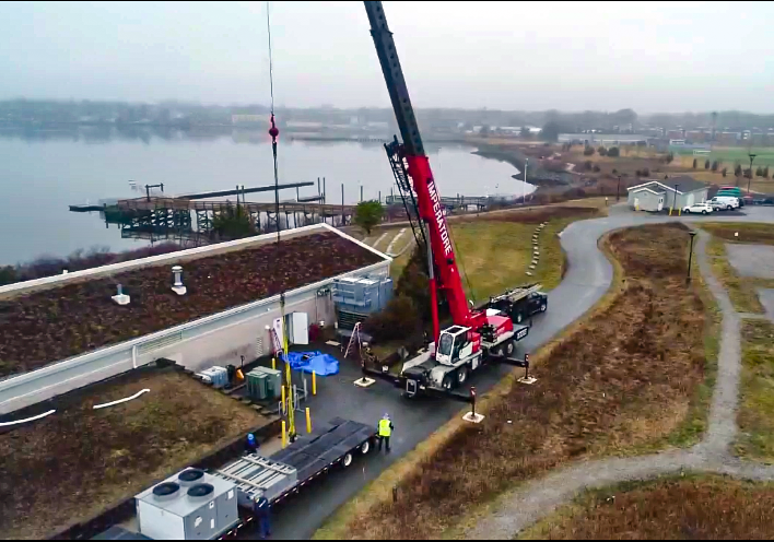 An aerial shot. In the foreground: A red crane parked in front of a long building lifts a large HVAC component off of a flatbed truck along the coast of Fields Point in Providence, R.I. In the background: A foggy pier extends into the waters off Fields Point.