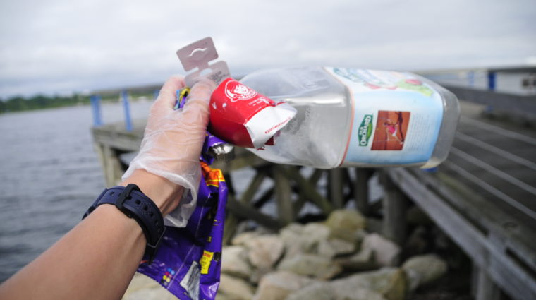 A volunteer displays plastic bottles and other debris during a Save The Bay cleanup.