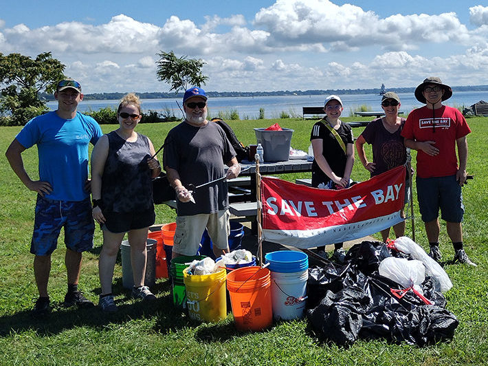 Six volunteers stand behind a pile of collected litter, holding a Save The Bay banner at Conimicut Point.