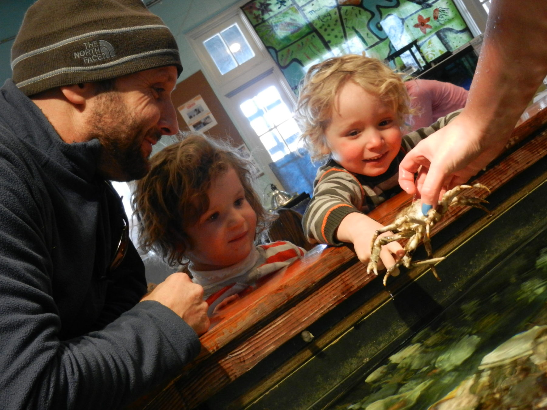 A dad and two kids at the Exploration Center and Aquarium