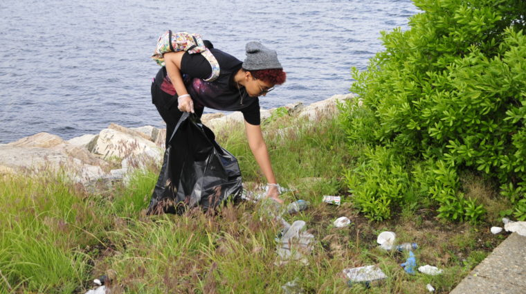 Volunteer collects trash at Collier Point.
