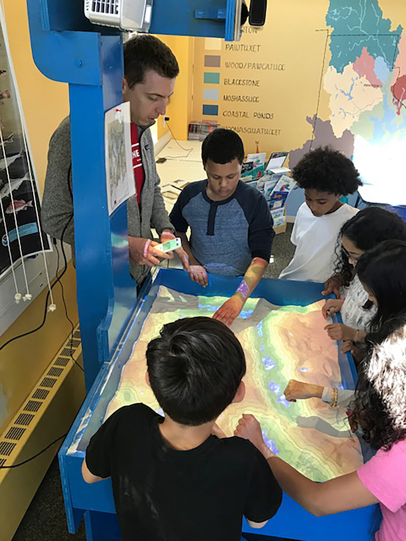 Educator Chris Dodge demonstrates watershed using the augmented reality sandbox
